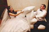 stock photo of pillow-fight  - Portrait of happy newlywed couple fighting with pillows on sofa - JPG