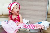 image of packing  - happy baby girl is going on a trip pack a suitcase - JPG