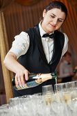 stock photo of bartender  - female waitress pour a glass of champagne during catering service at party - JPG