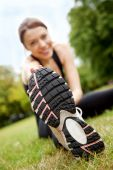 stock photo of workout-women  - Beautiful woman doing gym stretches on the grass outdoors - JPG