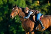 foto of saddle-horse  - Young woman riding a horse - JPG