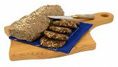 stock photo of biscuits  - Rustic gluten-free and dairy-free bread and biscuits on wooden chopping board with knife isolated on white. ** Note: Shallow depth of field - JPG