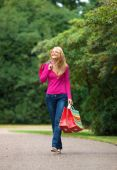 image of blonde woman  - Happy girl walking with bags at the park - JPG