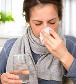 stock photo of allergy  - Sneezing woman into tissue - JPG