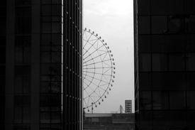 image of ferris-wheel  - Ferris wheel of Tokyo between buildings in black and white - JPG