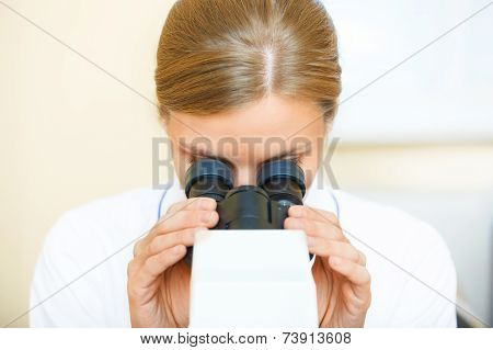 Woman Working With A Microscope.