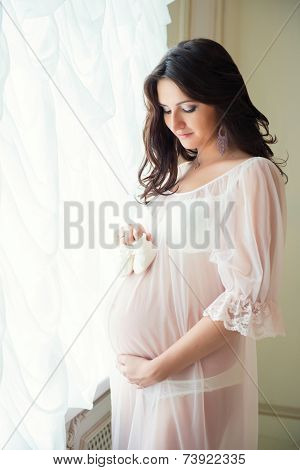 Tender Pregnant Mom In The Subtlest Peignoir Holding Baby Booties