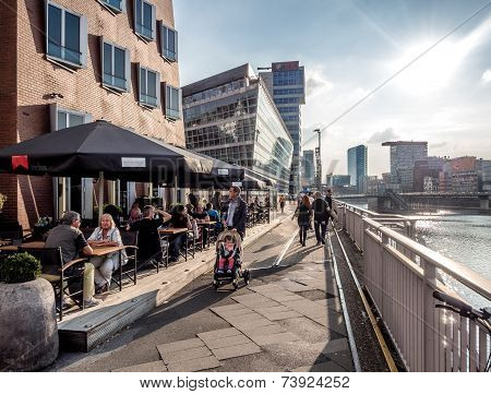 Tourists sitting in a sidewalk cafe in Dusseldorf Media Harbor