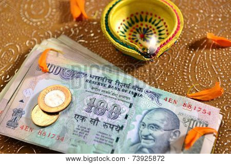 100 rupee bank notes and coins with indian traditional lamp.