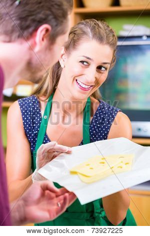 Saleswoman at organic supermarket counter offering customer cheese