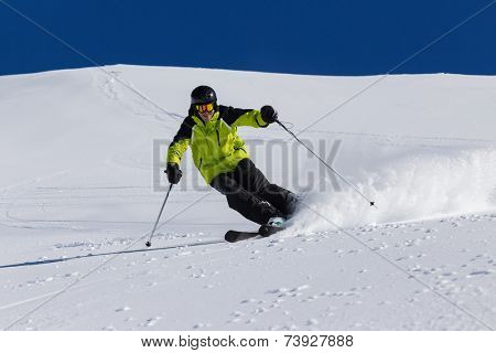 Alpine skier skiing downhill, blue sky on background