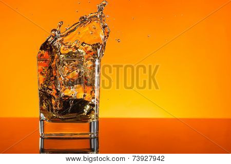Whiskey shot splashing out of glass on orange background