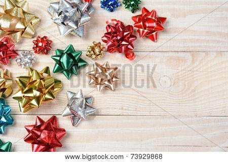 High angle shot of colorful holiday bows on a whitewashed rustic wood table. Horizontal format with copy space.