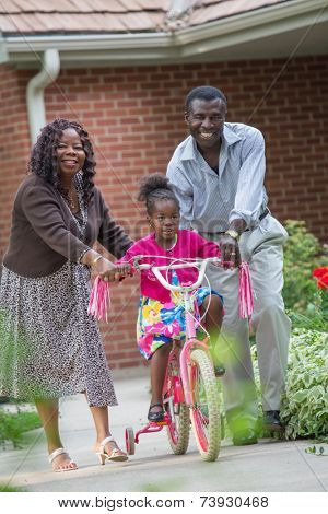 Smiling African American Grand Parents Helping Little Girl Biking Outdoor, grandpa and grand daughter