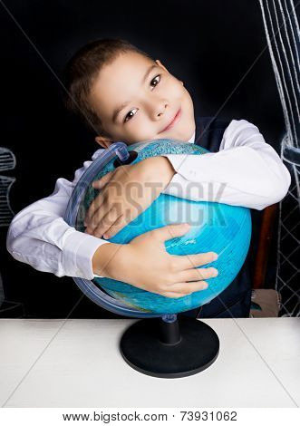 seven year old school boy sitting by the table with a globe