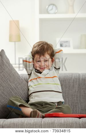 Portrait of smiling caucasian kid sitting on sofa at indoor home. Looking at camera.
