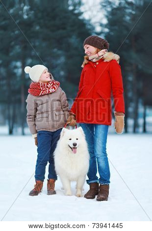 Beautiful Happy Family, Mother And Son Walking With White Samoyed Dog Outdoors In The Park