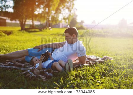 Happy Family, Dad And Son Resting In The Evening At Sunset In The Park On The Grass