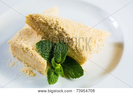 Cake Napoleon of puff pastry with sour cream on a plate.