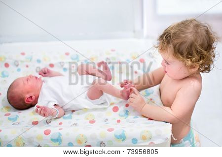 Portrait Of A Cute Curly Toddler Girl Playing With The Feet Of Her Newborn Baby Brother