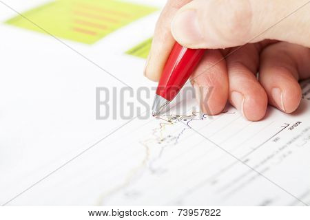 Close-up of female hand holding pen over business graph