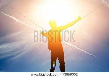 Silhouette of man rejoicing achievement raised the hands