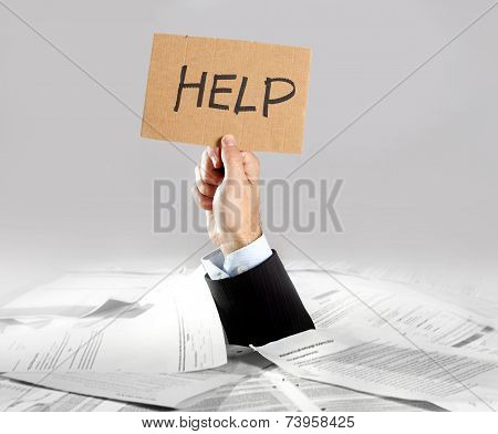 Hand Of  Businessman Emerging From Loaded Paperwork Desk Holding Help Message
