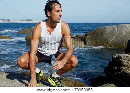 Male fit runner resting while sitting on rocks on the beach