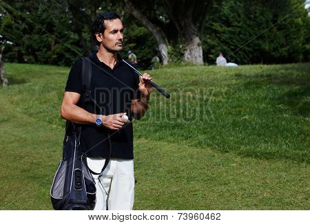 Handsome wealthy man in polo t-shirt standing on golf course