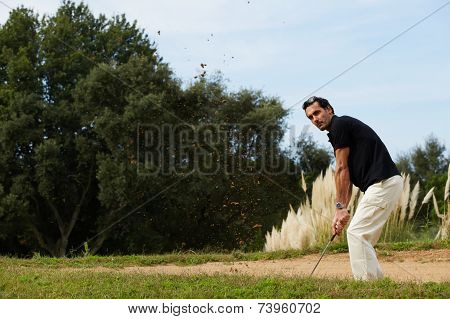 Handsome man hitting golf ball from golf sand trap