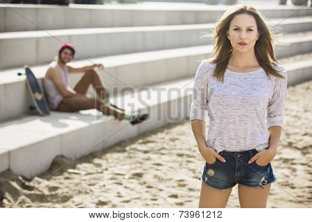 beautifull girl in front of the boulevard by the seaside with her skater boyfriend in the background
