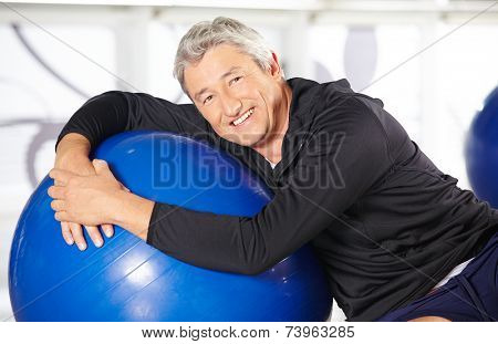 Smiling elderly man sitting with an exercise ball in a gym