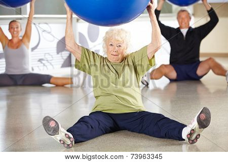 Senior woman doing back traing with gym ball in a fitness center