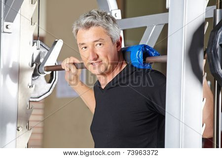Man lifting barbell in fitness center as part of his gym training