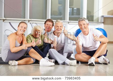 Group of happy senior people holding thumbs up in a gym