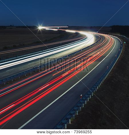 Vehicles on a highway traveling at night