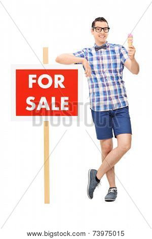 Full length portrait of a man holding an ice cream by a for sale sign isolated on white background