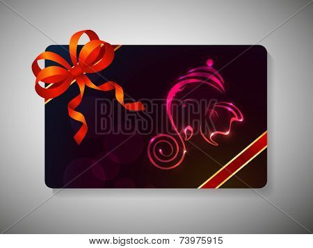 Diwali festival gift card with shiny face of Lord Ganesha and ribbon decoration on stylish background.