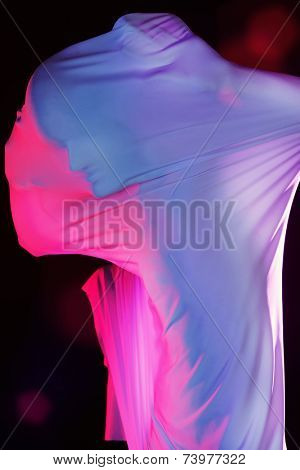 Art photo of a male silhouette breaking through the fabric. Horror. Struggle concept.