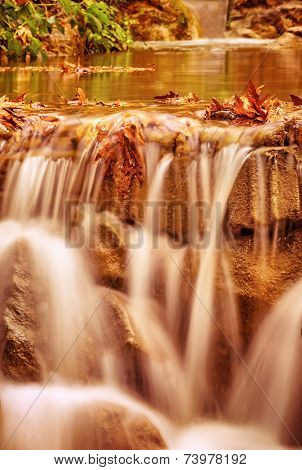 Beautiful little waterfall in the forest, autumn season, beautiful natural landscape, flowing river on the stones, beauty of nature concept