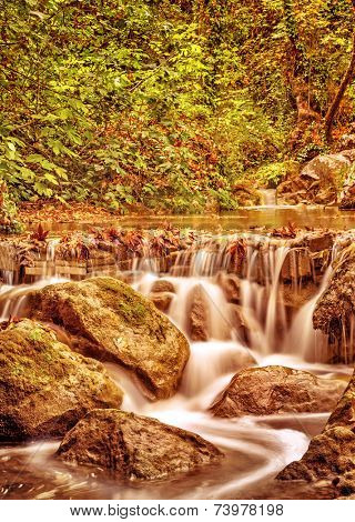 Waterfall in the autumn park, little mountainous wild river streaming in the forest, beauty of nature concept