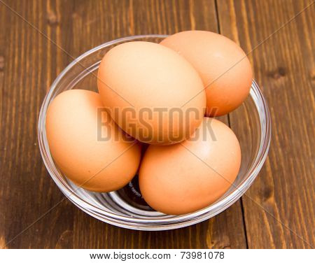 Eggs inside bowl on wood