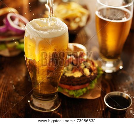 beer being poured into glass with gourmet hamburgers