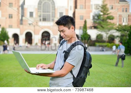 Happy male student use laptop at university campus