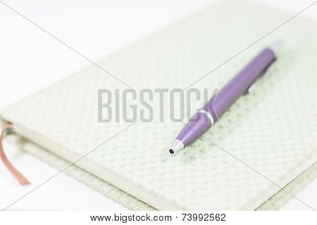 Closeup Notebook With Pen On White Background