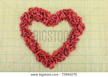 Goji berries organised in heart shape on bamboo mat background