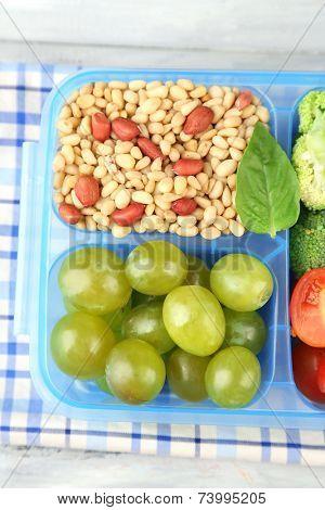 Tasty vegetarian food in plastic box on wooden table