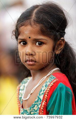 BATU CAVES, MALAYSIA, FEBRUARY 07, 2012: Serious Hindu girl portrait during the annual Thaipusam religious festival in Batu Caves, near Kuala Lumpur, Malaysia.