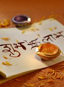 picture of swastik  - Indian traditional lamps placed on a book with Sanskrit calligraphy - JPG