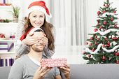 picture of give thanks  - young girl is giving her boyfriend a christmas gift in front of christmas tree  - JPG